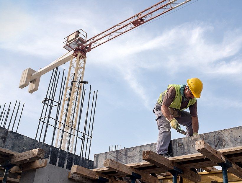 worker at construction site using hammer on beam